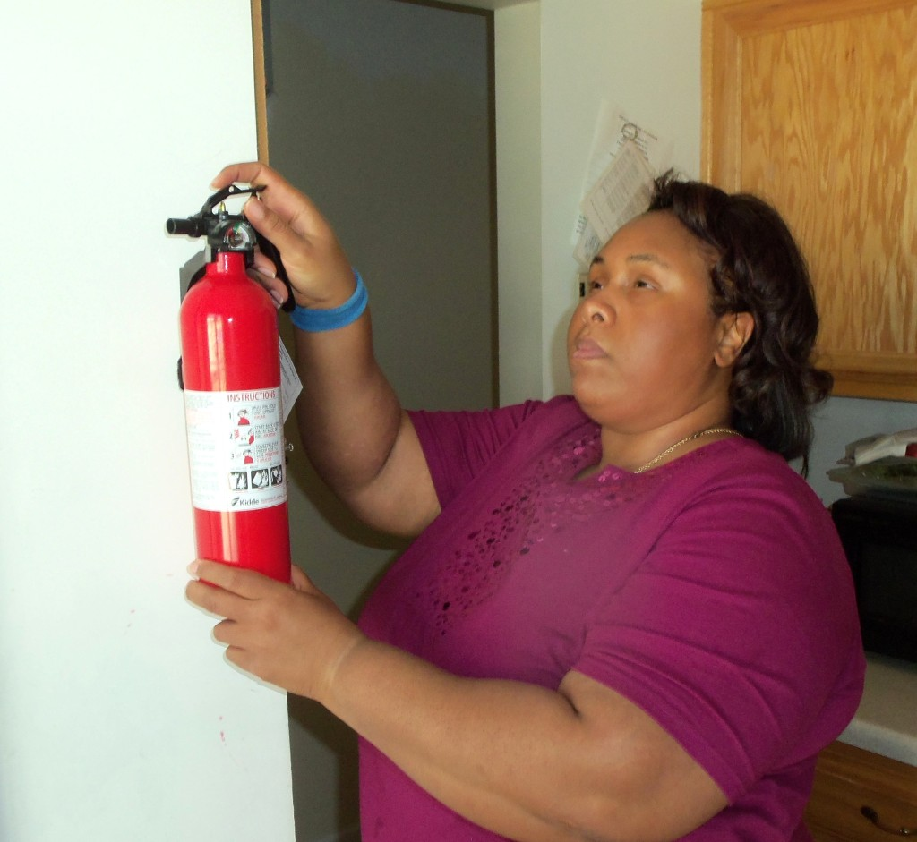 Empish Touching Fire Extinguisher Mounted on Wall