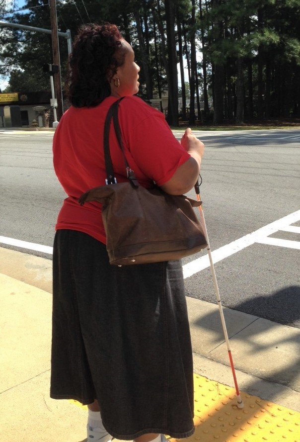 Empish Holding White Cane at Street Intersection