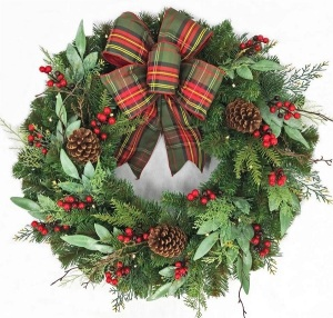 A Christmas wreath with a red and green plaid bow, red berries, pine cones and three different kinds of greenery.