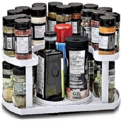A white plastic two-level spice rack with a variety of spices and containers.