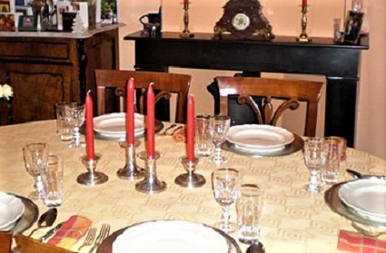 A dining table set with 5 place settings, crystal, and candles