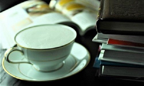 Books on desk with cup of tea