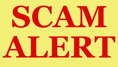 """Inside a sign with a yellow background and red border are The words """"SCAM ALERT"""" in bold red letters."""