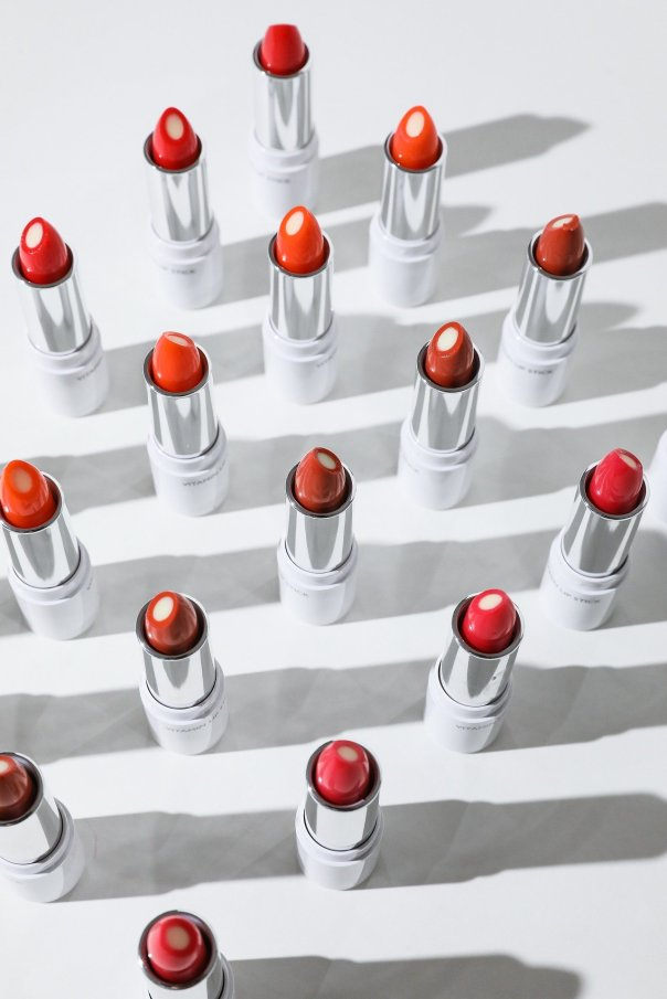 An aerial view of tubes of lipstick with a white background in shadows cast by each tube.