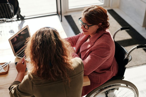 A woman in a wheelchair along side another woman working with her on a computer